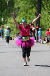 Mei running with her arms in the air at the Women's Half Marathon.