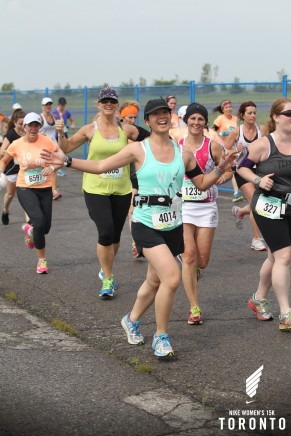 Mei running on the tarmac and looking excited with other runners.
