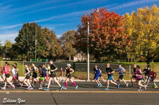 Runners with the leaves on the trees changing colour in the background.